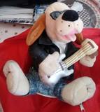 Perro de peluche guitarrista. - foto